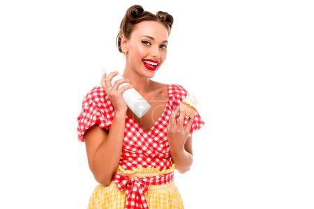 Photo for Smiling pin up girl holding cupcake and bottle with whipped cream isolated on white - Royalty Free Image