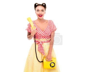 Photo for Beautiful pin up girl holding vintage yellow phone and looking at camera - Royalty Free Image
