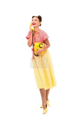 Photo pour Bel pin-up girl vintage téléphone jaune en se tenant sur des talons hauts - image libre de droit