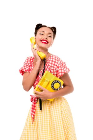 Photo pour Smiling happy pin up girl talking on vintage yellow phone - image libre de droit