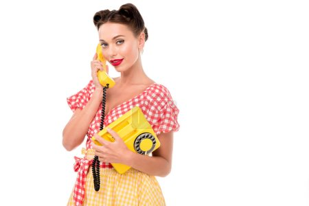 Photo pour Beautiful pin up girl talking on vintage yellow phone and looking at camera - image libre de droit