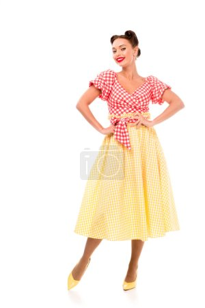 Photo for Elegant pin up girl in vintage clothes posing on high heels and holding hands on hips isolated on white - Royalty Free Image