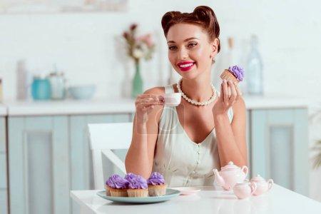 elegant gekleidetes Pin-up-Mädchen mit einer Tasse Kaffee und hausgemachtem Cupcake