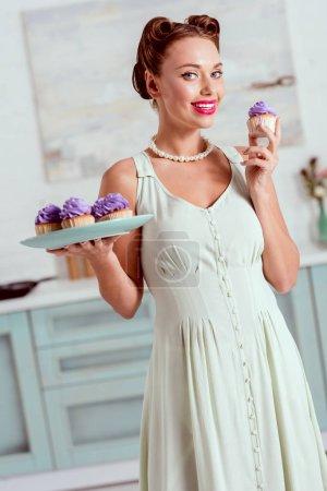 Photo pour Sourire de pin-up de fille avec assiette de petits gâteaux dans une main et unique cupcake dans d'autres - image libre de droit