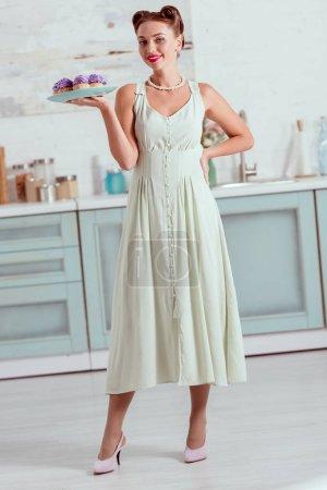 Elegant pin up girl in long dress holding plate full of homemade cupcakes