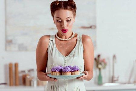 Photo pour Belle pin up fille regardant assiette pleine de petits gâteaux - image libre de droit