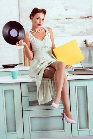Foto de Pin sonriente a chica sentada en la mesa y sosteniendo el disco de música de vinilo - Imagen libre de derechos