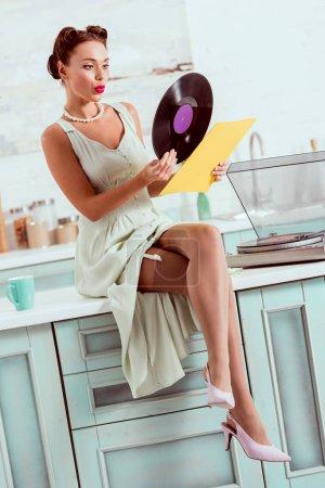 Photo pour Jolie pin-up girl assis sur la table avec les jambes croisées et obtenir le disque vinyle hors couverture - image libre de droit