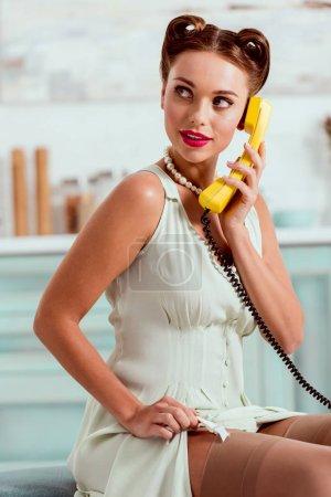 Photo pour Séduisante pin-up girl parler vintage téléphone jaune tout en bas de la fixation - image libre de droit