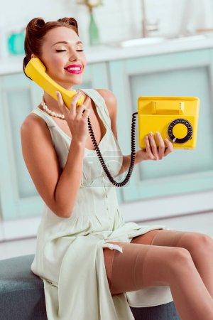 Foto de Hermoso pin encima de la muchacha sentada en otomano y hablando por teléfono vintage amarillo con los ojos cerrados - Imagen libre de derechos