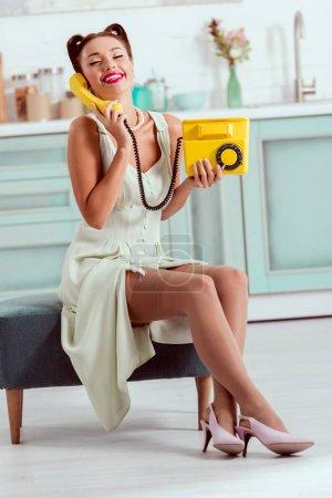 Foto de Sonriendo el perno encima de la chica sentada en otomano y hablando por teléfono amarillo vintage - Imagen libre de derechos
