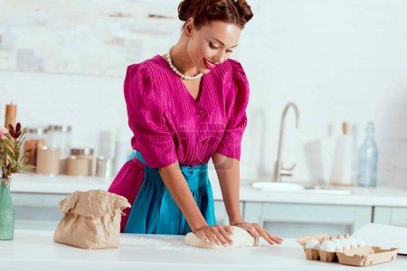 Elegantes Pin-up-Mädchen knetet Teig auf Küchentisch