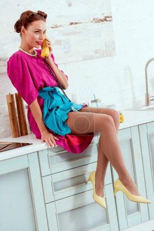Photo pour Séduisante pin-up girl assis sur la table de la cuisine et parler au téléphone jaune vintage - image libre de droit