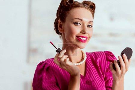 Photo pour Sourire pin up fille en robe cramoisi et collier de perles tenant visage poudre et baume à lèvres - image libre de droit