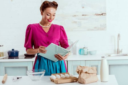 elegant gekleidete Pin-up-Mädchen lesen Rezepte Buch