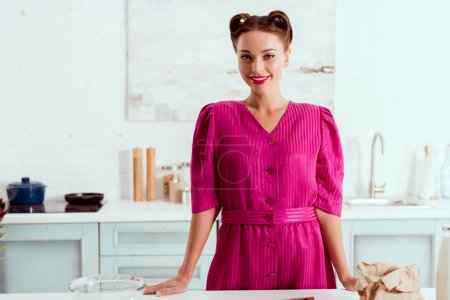 Photo for Beautiful smiling pin up girl standing by kitchen table - Royalty Free Image