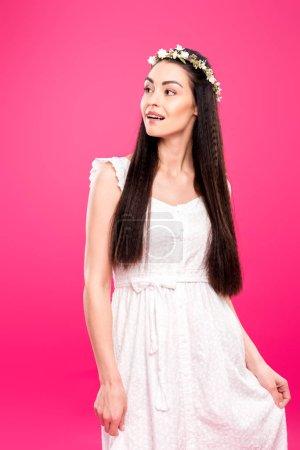 Foto de Feliz mujer morena joven en vestido blanco y guirnalda floral sonriendo y mirando a aislado en rosa - Imagen libre de derechos