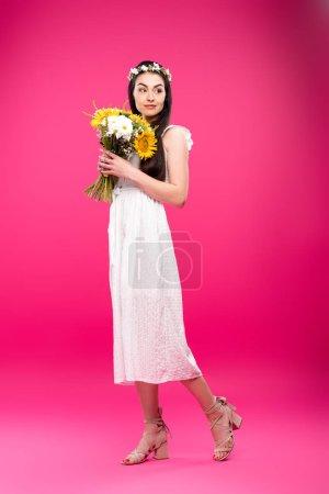 Photo pour Vue de la pleine longueur de belle femme brune en robe blanche et florale couronne tenant le bouquet rose - image libre de droit