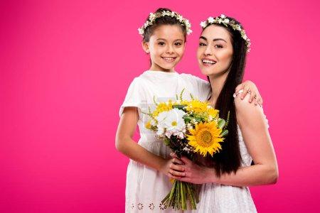 Foto de Hermosa feliz madre y su hija en vestidos blancos y guirnaldas florales con ramo de flores y sonriendo a cámara aislada en rosa - Imagen libre de derechos