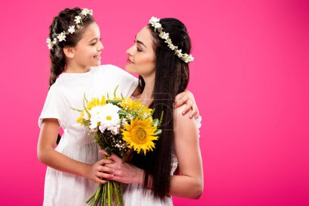 Photo for Beautiful happy mother and daughter in white dresses holding flower bouquet and smiling each other isolated on pink - Royalty Free Image