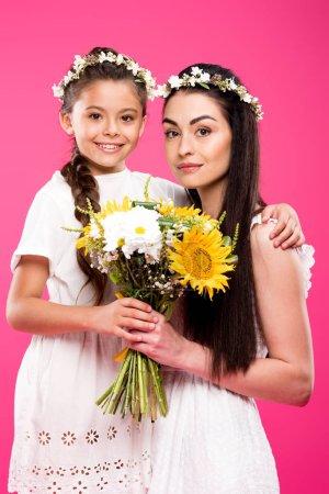 Foto de Hermosa feliz madre y su hija en vestidos blancos con ramo de flores y sonriendo a cámara aislada en rosa - Imagen libre de derechos
