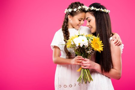 Photo for Beautiful happy mother and daughter in white dresses and wreaths holding flowers isolated on pink - Royalty Free Image