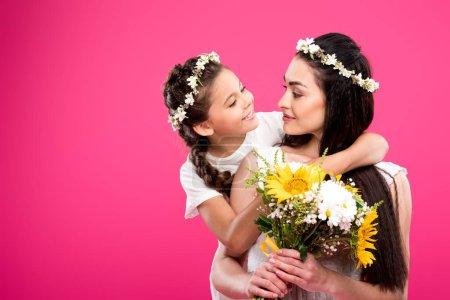 Foto de Adorable hija feliz mirando a la hermosa madre con ramo de flores aislada en rosa - Imagen libre de derechos