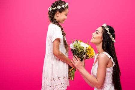 Photo for Side view of beautiful happy mother and daughter holding bouquet of flowers and smiling each other isolated on pink - Royalty Free Image