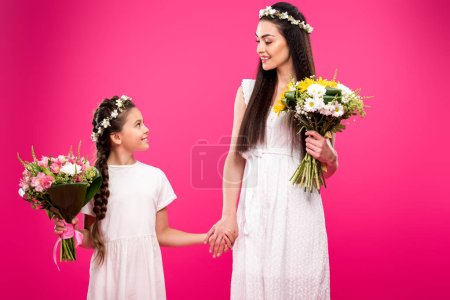 Photo for Beautiful happy mother and daughter in white dresses and floral wreaths holding bouquets and smiling each other isolated on pink - Royalty Free Image