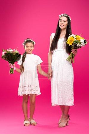 Foto de Vista de longitud completa de hermoso feliz madre e hija en vestidos blancos y guirnaldas florales sosteniendo Ramos y sonriendo a la cámara en color de rosa - Imagen libre de derechos