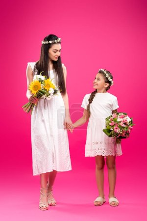 Photo for Full length view of beautiful mother and daughter in white dresses holding bouquets and smiling each other on pink - Royalty Free Image