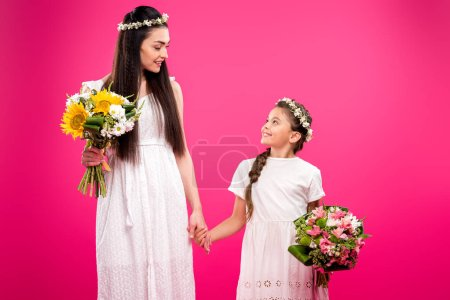 Photo for Beautiful mother and daughter in white dresses holding bouquets and smiling each other isolated on pink - Royalty Free Image