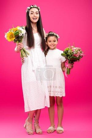 Foto de Feliz madre e hija en vestidos blancos y guirnaldas florales con hermosos Ramos de flores en rosa - Imagen libre de derechos
