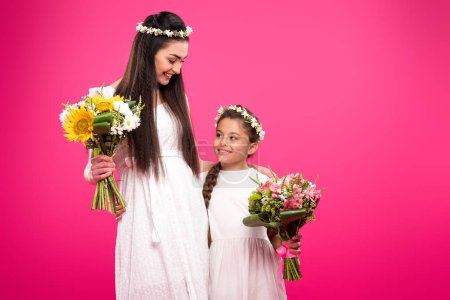 Photo for Beautiful happy mother and daughter in white dresses and floral wreaths holding bouquets isolated on pink - Royalty Free Image