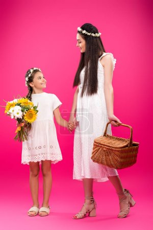 beautiful happy mother and daughter in white dresses holding bouquet and picnic basket on pink