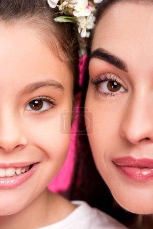 Schnappschuss der schönen glücklichen Mutter und Tochter im Blumenkranz, die in die Kamera lächeln, isoliert auf rosa