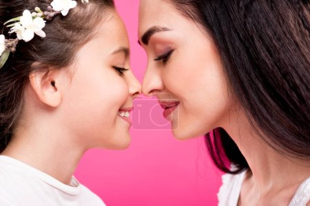 Photo for Side view of beautiful happy mother and daughter isolated on pink - Royalty Free Image