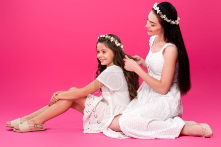 Photo for Happy young mother plaiting braid to beautiful smiling daughter on pink - Royalty Free Image