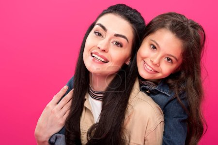 Photo for Beautiful happy mother and daughter hugging and smiling at camera isolated on pink - Royalty Free Image