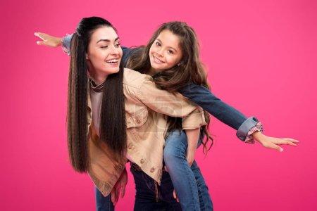 piękny szczęśliwy matka i córka piggybacking na białym tle na różowy