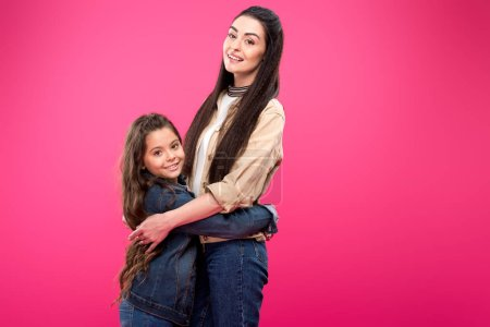 Photo for Side view of beautiful happy mother and daughter hugging and smiling at camera isolated on pink - Royalty Free Image