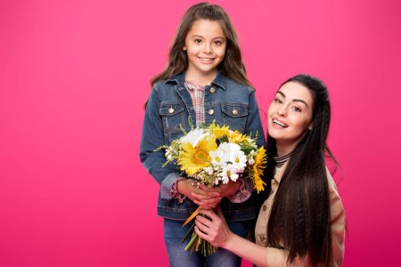 Photo for Beautiful happy mother and daughter holding bouquet of flowers and smiling at camera isolated on pink - Royalty Free Image