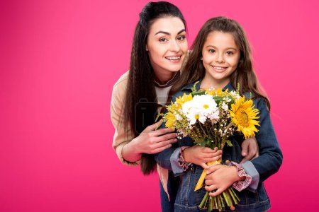 Photo for Happy mother and daughter holding beautiful bouquet of flowers and smiling at camera isolated on pink - Royalty Free Image