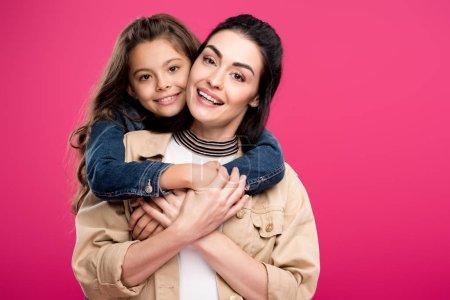 Photo pour Belle mère heureuse et fille étreignant et souriant à la caméra isolé sur rose - image libre de droit