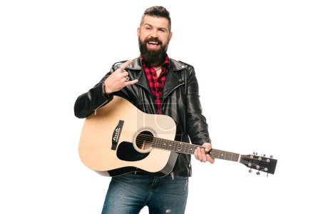 Photo for Handsome smiling musician in black leather jacket holding acoustic guitar and showing rock and roll sign, isolated on white - Royalty Free Image