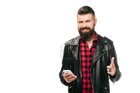 Photo for Happy bearded man in black leather jacket pointing and using smartphone, isolated on white - Royalty Free Image