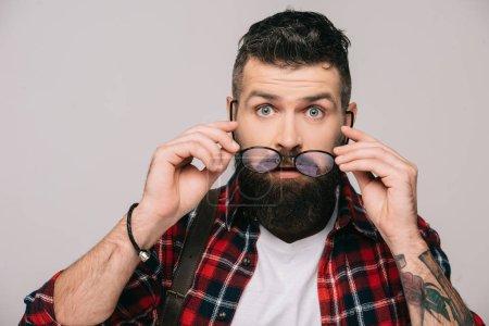 Photo pour Homme barbu surpris tenant des lunettes, isolé sur gris - image libre de droit
