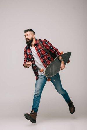 Photo pour Bel homme avec longboard isolé sur fond gris - image libre de droit