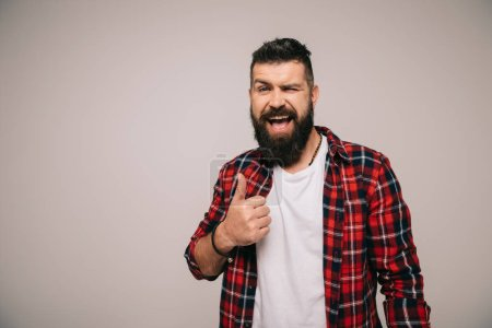 Photo for Excited bearded man winking and showing thumb up, isolated on grey - Royalty Free Image