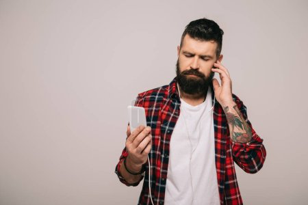 Foto de Hombre con barba en escuchar música de camisa a cuadros con auriculares y smartphone, aislado en gris - Imagen libre de derechos